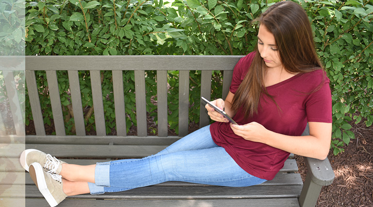 Teen girl sitting on a bench using tablet