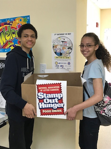 Two students holding a box for food donations