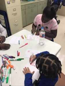 Students drawing pictures at a table